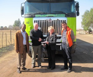 Louise Lindeque, Responsible Care manager, hands the Responsible Care certificate to Jacques de Norre, CEO of Sihlangene Bulk, while Thebe Magapa (left) and Peter Vera look on.