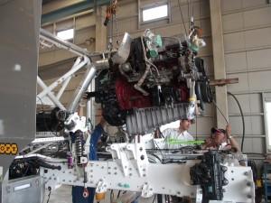 Hino Team Sugawara principal Yoshimasa Sugawara (bottom right) gives a hand with the installation of the modified 9-litre turbo diesel engine.