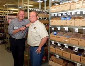 Dealer Principal Patrick Arthur (left) shows customer Bernard Basson, logistics manager of International Slab Sales, the vast array of parts held in stock at the dealership.