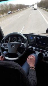 This truck is in a 'platoon' with the truck in front of it. Truck platooning is the linking of two or three trucks in a convoy. These vehicles closely follow each other at a set distance by using connectivity technology and automated driving support systems. Note the driver's hands are off the steering wheel. This is autonomous driving linked to truck platooning.