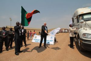 Simon Cammelbeeck, country director of World Food Programme-Zambia, along with Patrick Kangwa, permanent secretary of Zambia's Disaster Mitigation and Management Unit, wave off the convoy of trucks as they set off for Malawi and Zimbabwe.