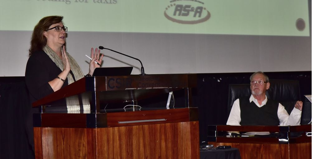 Alta Swanepoel addresses a packed audience at the last of the three 2016 Transport Legislation workshop events as Max Braun, chairman of the workshop, looks on.