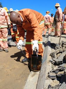 """Executive Mayor of the city of Johannesburg, Herman Mashaba, along with a number of city officials, took to the streets of Ivory Park and Midrand to launch his """"war' against potholes. Here he gets down and dirty as he joins one of the pot-hole repair teams on site."""