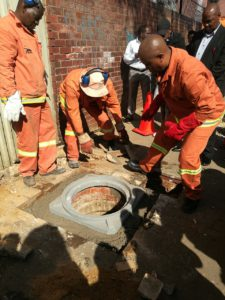The Executive Mayor of the City of Johannesburg, Herman Mashaba (right), gets stuck in helping his maintenance crew replace the first of 4 000 manhole covers around the city.