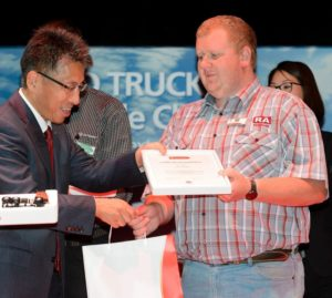 Lafras Kruger receives his first prize award in the Quester category from Kishi Nobuhiko, UD Trucks' senior vice president of brand and product. Well done World Champ!