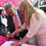 Minister-Counsellor from the Japanese Embassy, Shuichiro Kawaguchi, signs the deal for the donation of two new vehicles to PinkDrive. With him is Noelene Kotschan, CEO and Founder of PinkDrive.