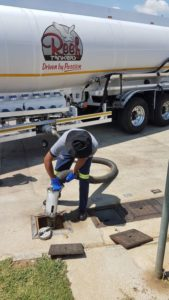 Priest Mufhadi, Bulk Truck Operator with Reef Tankers, connects the hose from the tanker to the receiving tank in the ground. All safety standards had been adhered to before linking up.