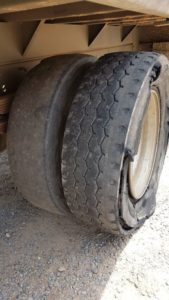 A burst tyre next to a bald, illegal tyre with a cut on the inner sidewall. The tyre burst would have happened on the trip but a pre-trip inspection by the driver would have highlighted the dangerous inner tyre. There was no safety margin here.