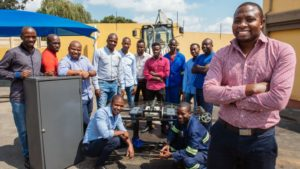 Clement Mokoenene and his team with the Vehicle Energy Harvesting System (VEHS). The system is fitted below the road surface with the vehicles driving over it creating the pressure that powers a turbine. A two kilometre stretch of highway fitted with the system could potentially power an entire city.
