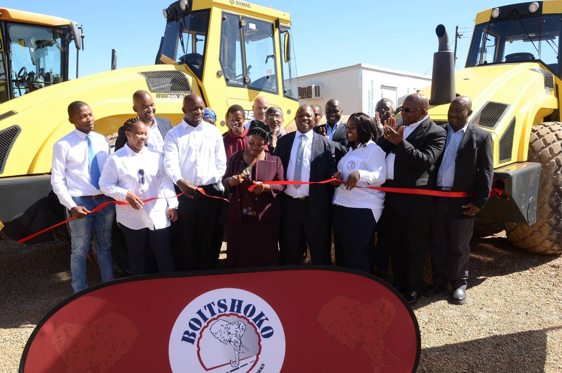 "Founding member of Boitshoko Road Surfacing and Civil Works, Mrs Makume (centre), cuts the celebratory ribbon along with managing director, Dr N Phillip Makume and staff. ""With this new relationship and with Bell and SANRAL's support, we feel blessed to now have the ability to compete meaningfully in this challenging road construction industry,"" says Dr Makume."