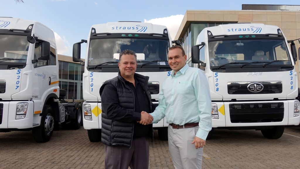 Eugene van der Berg (left), regional general manager of FAW South Africa, congratulates Wayne Greenwood, managing director of Choice Diesel Mozambique, on their appointment as the FAW Mozambique dealer. Behind them are three of the 44 FAW 33.420FT truck tractors bought by Strauss Logistics.