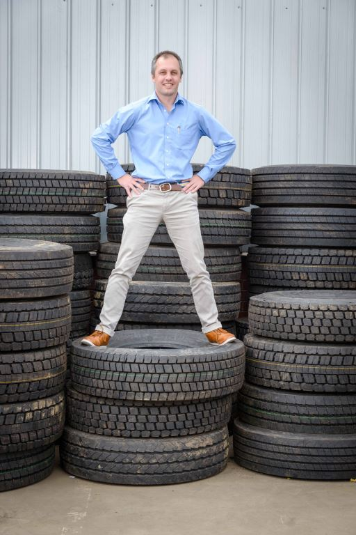 """Dr Mehran Zarrebini, CEO of British investment group PFE International, one of the largest investors in the Mathe Group, stands on a pile of truck tyres waiting for recycling. """"Ours will be the first facility to process both whole tyres and retreads for various industries including Van Dyck Carpets' factory,"""" he says."""