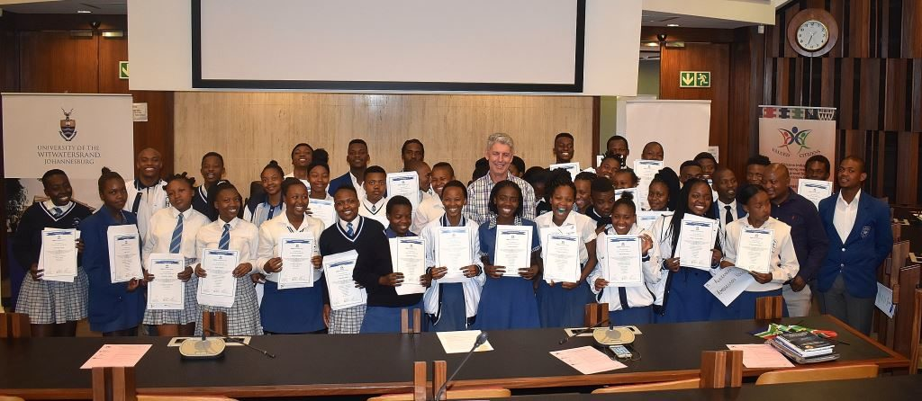"Achievers one and all. Grade 12 learners from Alexandra High proudly hold their VCI certificates with Len Brand, Executive Director of TATA International, in the center. ""Tata aims to do business in a manner that uplifts and creates entrepreneurs and leaders, because if you create leaders, they tend to uplift communities automatically,"" were Brand's words."