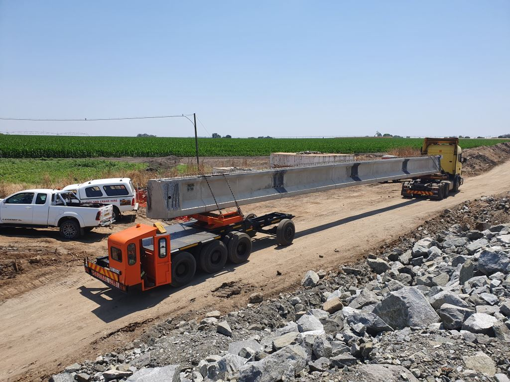 Each 26 ton beam for the dualling of the N4 bridge crossing the Crocodile river is individually transported by a truck tractor on the one side and a steering trailer on the other.