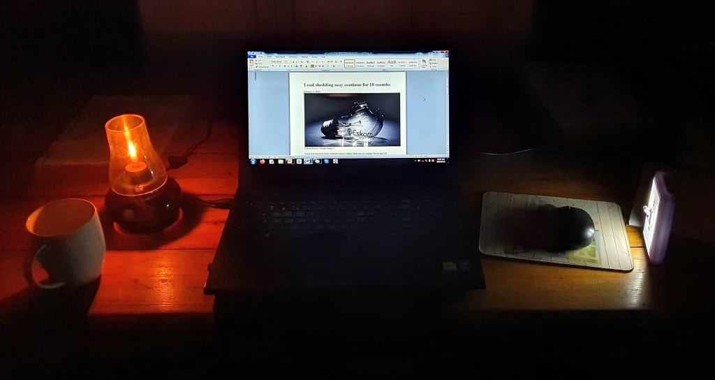 Due to Eskom power blackouts, this was my work environment most nights with a candle and a battery powered portable light on each side of the laptop to help the fingers find their way on the keyboard. The productive time lasted only as long as the laptop battery held its power – which was not long at all. Laptop batteries are as useless as Eskom.