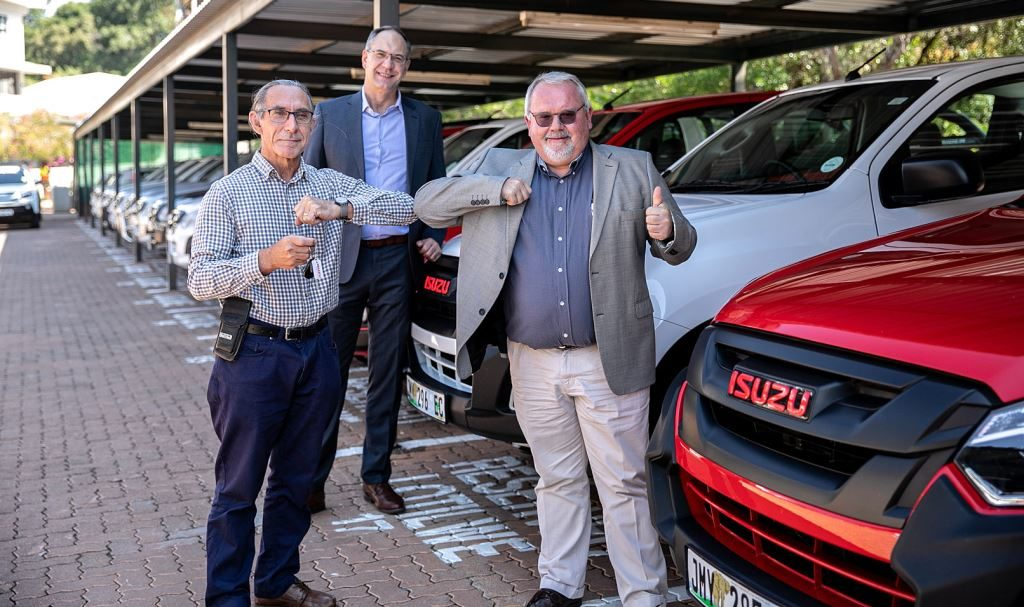 Nudging elbows during the handover of 15 Isuzu D-MAX bakkies to the Faculty of Health Sciences at the University of Pretoria are Professor Jannie Hugo (left), Head of the Department of Family Medicine at the university and Tim Hendon, Isuzu Motors South Africa marketing manager. Professor Tiaan de Jager, Dean of the Faculty of Health Sciences at the University of Pretoria can be seen peeking over from the back.