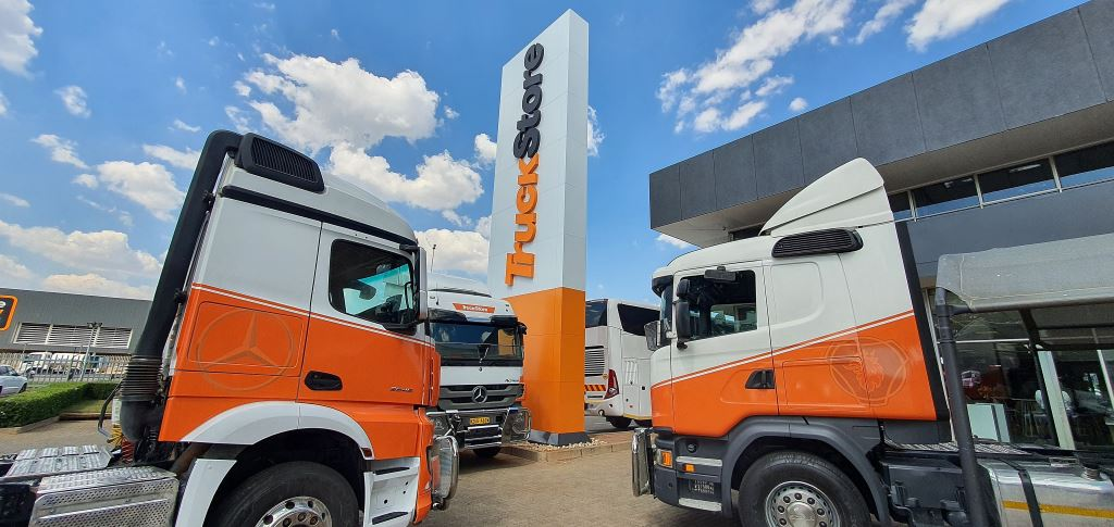 An impressive display of used trucks and a bus parked around the prominent tower TruckStore sign heralded in the opening of the new facility.