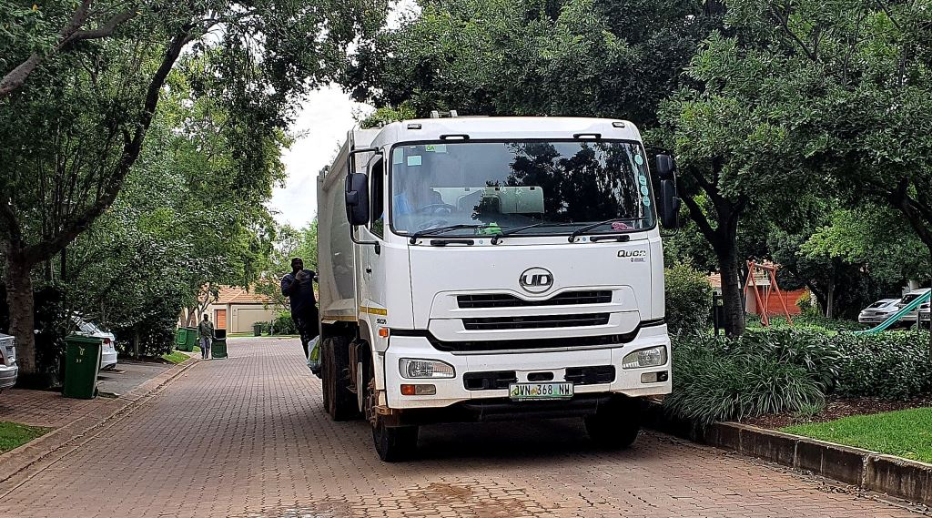 A UD Quon refuse compactor at work. With Isuzu Motors now owning UD Trucks, do we buy a UD Quon or an Isuzu F-Series to take our junk away – and from which dealer?